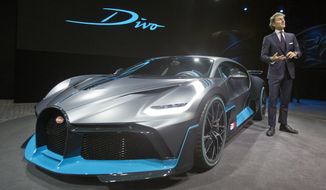 President of Bugatti Automobiles S.A.S. Stephan Winkelmann gestures as he speaks next to a 5 million euro (5.8 $) Bugatti Divo during a media presentation on the eve of Paris Auto Show in Paris, Monday, Oct. 1, 2018. Doubts about diesel, Brexit, trade worries, tighter emissions controls. Those are the challenges that will be on the minds of auto executives when they gather this week ahead of the Paris Motor Show at the Porte de Versailles exhibition center. (AP Photo/Michel Euler)