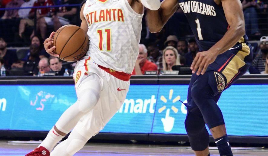 Atlanta Hawks rookie guard Trae Young (11) drives the lane with New Orleans Pelicans guard Jarrett Jack defending during the second half of a preseason basketball game Monday, Oct. 1, 2018, in Atlanta. The Hawks won 116-102. (AP Photo/John Amis)