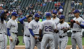 Texas Rangers' Adrian Beltre (29), is greeted by teammates before walking off the field during the fifth inning of a baseball game against the Seattle Mariners after he was replaced by Jurickson Profar at third base, Sunday, Sept. 30, 2018, in Seattle. (AP Photo/Ted S. Warren)