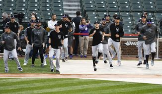 The Colorado Rockies warm up before a National League wild-card playoff baseball game against the Chicago Cubs, Tuesday, Oct. 2, 2018, in Chicago. (AP Photo/David Banks)