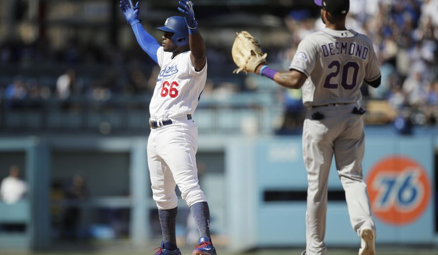 Los Angeles Dodgers' Yasiel Puig, left, reacts to his double as Colorado Rockies' Ian Desmond watches during the fourth inning of a tiebreaker baseball game, Monday, Oct. 1, 2018, in Los Angeles. (AP Photo/Jae C. Hong)