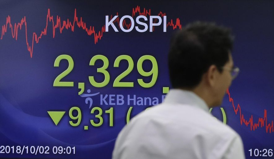 A currency trader walks by the screen showing the Korea Composite Stock Price Index (KOSPI) at the foreign exchange dealing room in Seoul, South Korea, Tuesday, Oct. 2, 2018. Asian shares fell on Tuesday as relief that the United States had brokered a trade deal with Canada gave way to concerns that negotiations with China were at a standstill. (AP Photo/Lee Jin-man)