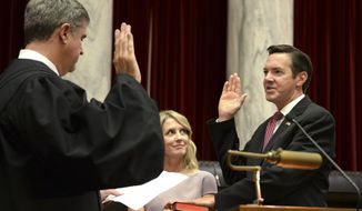 Evan Jenkins takes the oath of office Monday, Oct. 1, 2018 for the West Virginia Supreme Court in Charleston, W.Va. Jenkins and former House Speaker Tim Armstead have been appointed to serve as temporary justices until a Nov. 6 special election to replace Ketchum and Davis. Jenkins and Armstead are among 20 total candidates seeking those seats. (Kenny Kemp/Charleston Gazette-Mail via AP)