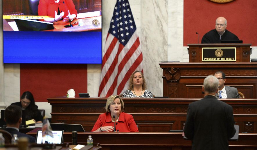 """West Virginia House Judiciary Chairman John Shott, right, back to camera, questions Supreme Court Justice Beth Walker, center, during her Impeachment trial in Charleston, W.Va. A West Virginia Supreme Court justice says her impeachment trial should never have happened. Walker testified Monday she thinks impeachable offenses include stealing, lying and corruption. She says, """"I don't think I've done any of those things."""" (Kenny Kemp/Charleston Gazette-Mail via AP)"""