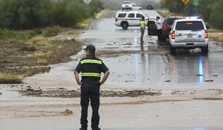 A tow truck driver eyes a flooded section of a road during rain in Tucson, Ariz., Monday, Oct. 1, 2018. Tropical Storm Rosa soaked northwestern Mexico with heavy rains as it neared the Baja California Peninsula on Monday and was projected to extend into a drenching of the U.S. Southwest. (Rick Wiley/Arizona Daily Star via AP)