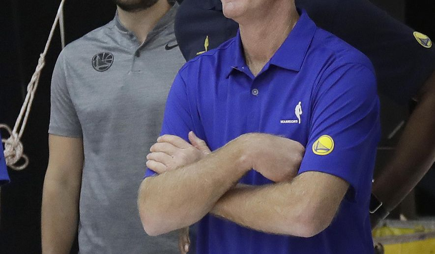 In this Sept. 24, 2018 photo, Golden State Warriors head coach Steve Kerr, foreground, waits to have photos taken with assistants Chris DeMarco, left, and Jarron Collins during media day at the NBA basketball team's practice facility in Oakland, Calif. Even the two-time defending NBA champions are seeking ways to reinvent themselves when it comes to preparation and practice routine. The Warriors are putting a greater emphasis on player development this training camp with a younger roster. (AP Photo/Jeff Chiu)