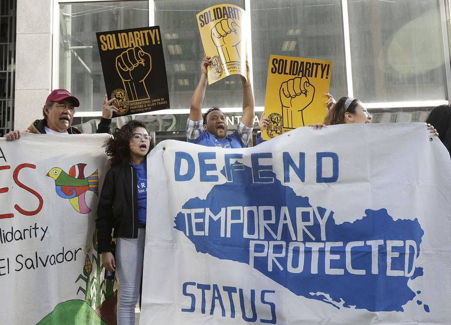 FILE - In this March 12, 2018 file photo, supporters of temporary protected status of immigrants cheer, hold signs and a banner with the outline of El Salvador at a rally at a federal courthouse in San Francisco, the day a lawsuit was filed against the Trump administration over its decision to end a program that lets immigrants live and work legally in the United States. During a hearing on Tuesday, Sept. 25, 2018, U.S. District Judge Edward Chen questioned the Trump administration's motives to end the program and repeated the president's vulgar language to describe some countries during a White House meeting in January. Chen is deciding whether to block the administration's decision to end temporary protected status for people from Sudan, Nicaragua, Haiti, and El Salvador. He did not immediately rule. (AP Photo/Jeff Chiu, File)