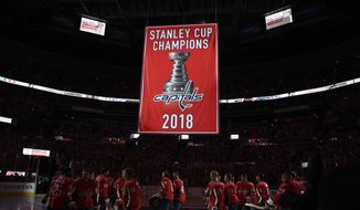 Washington Capitals skate on the ice as the team's Stanley Cup championship banner is raised before the team's NHL hockey game against the Boston Bruins, Wednesday, Oct. 3, 2018, in Washington. (AP Photo/Nick Wass)