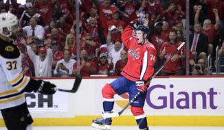 Washington Capitals defenseman John Carlson (74) celebrates his goal, near Boston Bruins center Patrice Bergeron (37) during the second period of an NHL hockey game Wednesday, Oct. 3, 2018, in Washington. (AP Photo/Nick Wass)