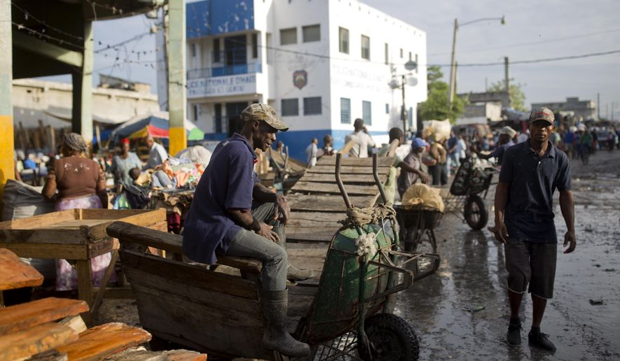 A worker sits on his wheelbarrow while waiting for customers in downtown of Port-au-Prince, Haiti, Wednesday, Oct. 3, 2018. ( AP Photo/Dieu Nalio Chery) ** FILE **