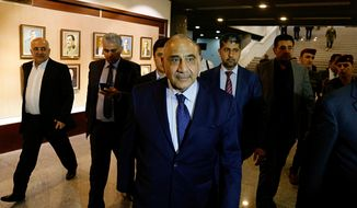 Iraqi Prime Minister Adel Abdul-Mahdi, center, leaves the parliament building in Baghdad, Iraq, Tuesday, Oct. 2, 2018. (AP Photo/Karim Kadim) ** FILE **