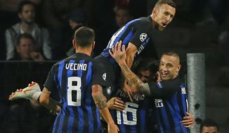 Inter midfielder Radja Nainggolan jumps on top of Inter midfielder Matteo Politano after they scored their side's second goal during a Group B Champions League soccer match between PSV and Inter Milan at the Philips stadium in Eindhoven, Netherlands, Wednesday, Oct. 3, 2018. (AP Photo/Peter Dejong)