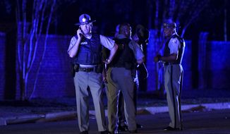 South Carolina state troopers gather on Hoffmeyer Road near the Vintage Place neighborhood where several law enforcement officers were shot, one fatally, Wednesday, Oct. 3, 2018, in Florence, S.C. (AP Photo/Sean Rayford)