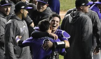 Colorado Rockies catcher Tony Wolters, rear, and left fielder Gerardo Parra, front, celebrate their win against the Chicago Cubs in the National League wild-card playoff baseball game, Wednesday, Oct. 3, 2018, in Chicago. The Rockies won 2-1. (AP Photo/David Banks)