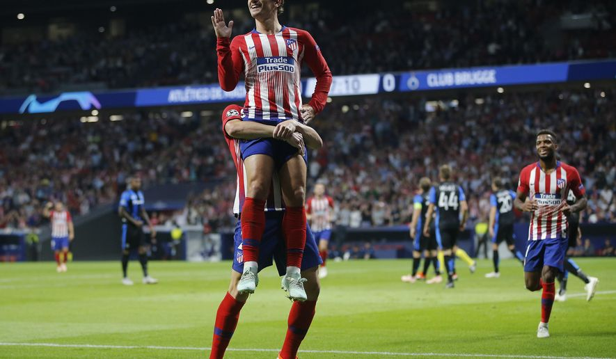 Atletico forward Antoine Griezmann, front, gestures as he is lifted in the air by Atletico defender Diego Godin, after he scored his side opening goal during a Group A Champions League soccer match between Atletico Madrid and Club Brugge at the Wanda Metropolitano stadium in Madrid, Spain, Wednesday Oct. 3, 2018. (AP Photo/Paul White)
