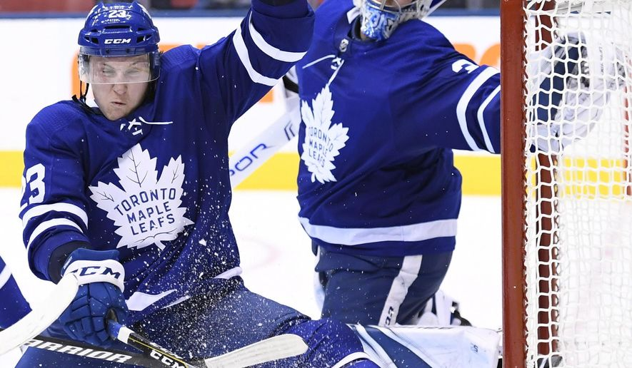 Toronto Maple Leafs defenseman Travis Dermott (23) gets his glove on the puck to make a save on a Montreal Canadiens shot as Maple Leafs goaltender Frederik Andersen (31) watches during the third period of an NHL hockey game Wednesday, Oct. 3, 2018, in Toronto. (Nathan Denette/The Canadian Press via AP)
