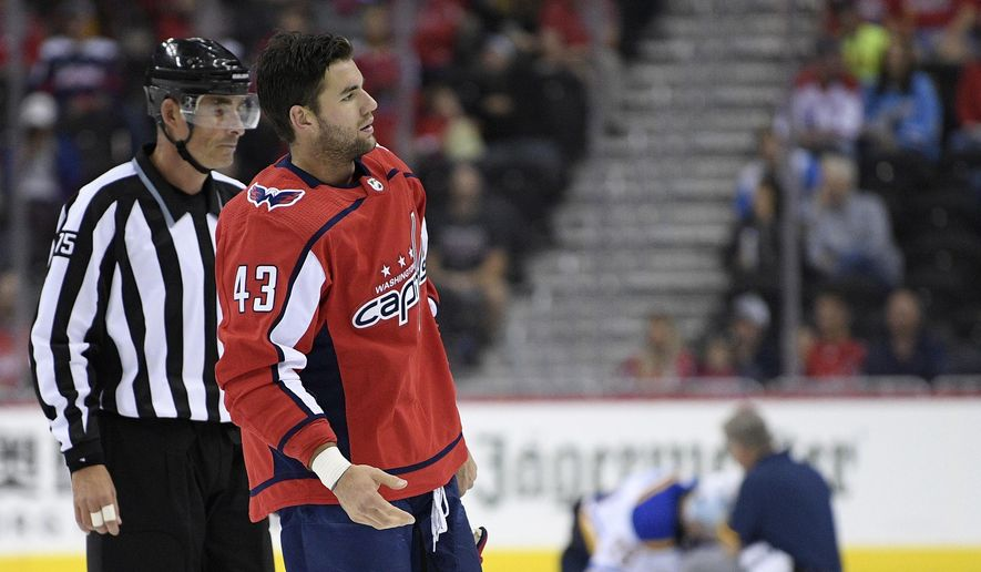 In this Sept. 30, 2018, file photo, Washington Capitals right wing Tom Wilson (43) is escorted by an official off the ice after he checked St. Louis Blues center Oskar Sundqvist, on ice at back center, during the second period of an NHL preseason hockey game, in Washington. Wilson has been suspended 20 games by the NHL for a blindside hit to the head of an opponent during a preseason game. Wilson's punishment was announced Wednesday, Oct. 3, 2018, just hours before the reigning Stanley Cup champion Capitals were to raise their banner and open their title defense by hosting the Boston Bruins to begin the regular season. (AP Photo/Nick Wass) ** FILE **