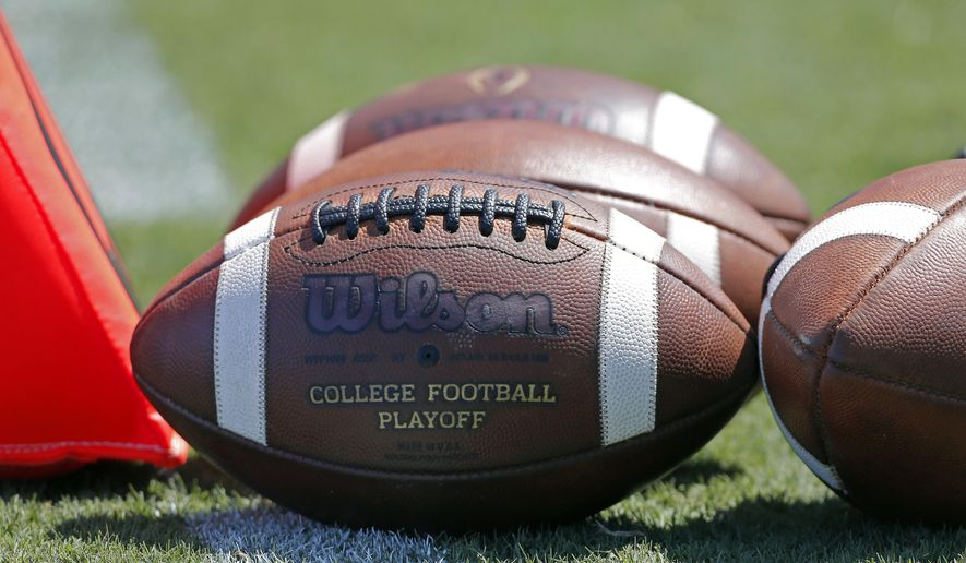 """FILE - In this Sept. 2, 2017, file photo, footballs sit on the turf ready for kick-off before the start of an NCAA football game between South Carolina and North Carolina State in Charlotte, N.C. A study from The Institute for Diversity and Ethics (TIDES) finds that white men still """"overwhelmingly"""" fill leadership positions at top-level college sports programs and conferences, leaving a """"consistent underrepresentation of women and people of color"""" in those roles. (AP Photo/Bob Leverone, File)"""