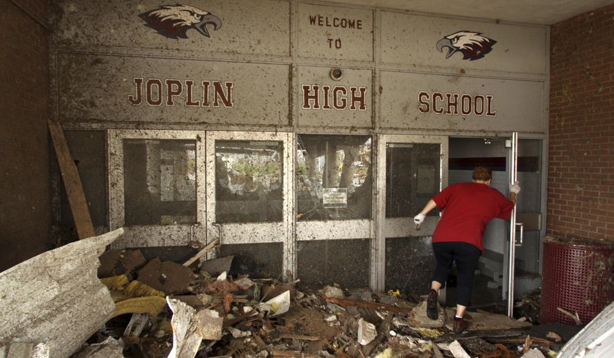 FILE - In this May 24, 2011, file photo, a woman makes her way into the main entrance of Joplin High School in Joplin, Mo., that was destroyed by a tornado. An Associated Press analysis has found that tardiness in filing appeals to be reimbursed by the federal government after disasters has been the top reason why Federal Emergency Management Agency headquarters has denied appeals from cities, schools and other entities over the past year. The denied appeals include a total of $67 million sought by the tornado-ravaged schools of Joplin. (AP Photo/Mark Schiefelbein, File)
