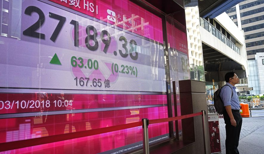A man stands in front of an electronic board showing the Hong Kong share index outside a local bank in Hong Kong, Wednesday, Oct. 3, 2018. (AP Photo/Vincent Yu)
