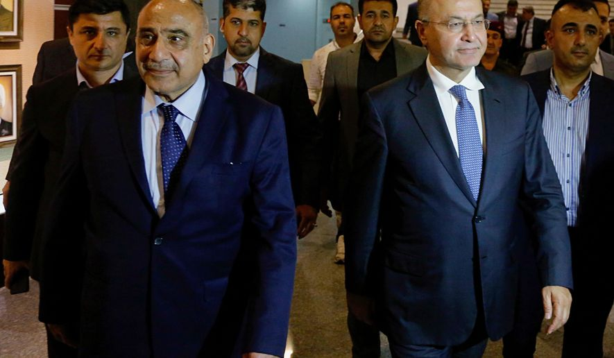 Iraq's new President Barham Salih, center right, walks with new Prime Minister Adel Abdul-Mahdi, center left, in the parliament building in Baghdad, Iraq, Tuesday, Oct. 2, 2018. Iraq's new president has tasked veteran Shiite politician Abdul-Mahdi with forming a new government nearly five months after national elections were held, state TV reported late Tuesday. (AP Photo/Karim Kadim)