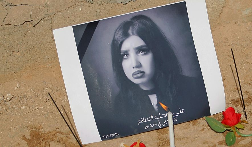 In this Monday, Oct. 1, 2018 photo, fans of slain former beauty queen, fashion model and social media star Tara Fares left flowers and  candles at her gravesite, in Najaf, Iraq. Fares won fame in conservative, Muslim-majority Iraq with outspoken opinions on personal freedom. Last week, she was shot and killed at the wheel of her white Porsche on a busy Baghdad street. The violence reverberated across Iraq and follows the slaying of a female activist in the southern city of Basra and the mysterious deaths of two well-known beauty experts. (AP Photo/Anmar Khalil)