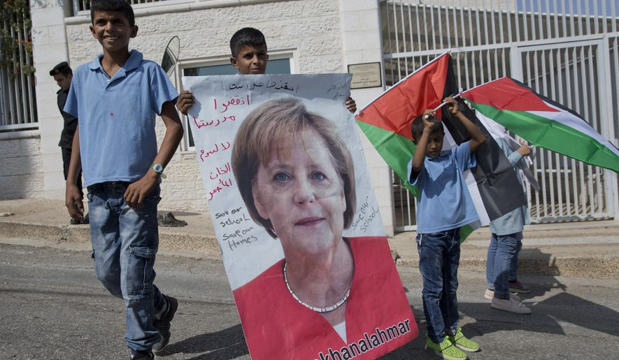 """Bedouin child from Khan al-Ahmar holds poster of German Chancellor Angela Merkel and Palestinian flags infront of the German representative office, in the West Bank city of Ramallah, Wednesday, Oct. 3, 2018. The children are pleading with Merkel to pressure Israel to halt demolition plans for the encampment outside an Israeli settlement east of Jerusalem. Arabic on the poster reads, """"save Khan al-Ahmar"""" and """"save our school."""" (AP Photo/Nasser Nasser)"""