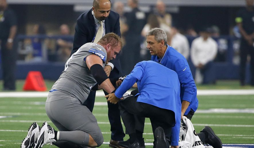 Detroit Lions offensive guard T.J. Lang, left, is attended to after an injury in the first half of an NFL football game against the Dallas Cowboys in Arlington, Texas, Sunday, Sept. 30, 2018. (AP Photo/Roger Steinman)