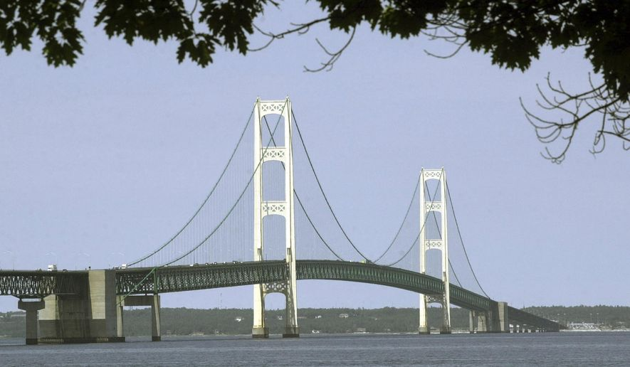 FILE - This July 19, 2002, file photo, shows the Mackinac Bridge that spans the Straits of Mackinac from Mackinaw City, Mich. Officials tell The Associated Press that Michigan Gov. Rick Snyder's administration and Canadian pipeline giant Enbridge have reached a deal on replacing 65-year-old twin pipelines in a channel linking two of the Great Lakes. An announcement was scheduled for Wednesday Oct. 3, 2018. Officials tell the AP the agreement calls for shutting down the Line 5 pipes in the Straits of Mackinac connecting Lakes Huron and Michigan. (AP Photo/Carlos Osorio, File)
