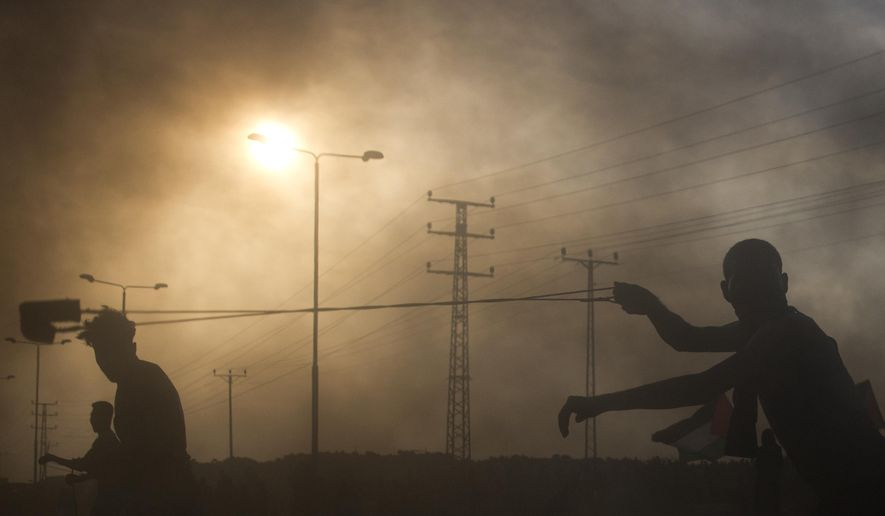 Palestinian protesters hurl stones during a demonstration at the entrance of Erez border crossing between Gaza and Israel, in the northern Gaza Strip, Wednesday, Oct. 3, 2018. (AP Photo/Khalil Hamra)