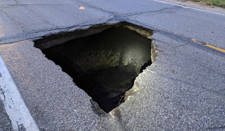 This undated photo provided by the Iowa State Patrol shows 9-by-8-foot hole in Highway 69 north of Jewell, Iowa. Iowa road officials have closed a section of the highway in central Iowa's Hamilton County after several drivers hit the massive sinkhole. The hole was reported sometime between 4 a.m. and 5 a.m. Wednesday Oct. 3, 2018, after multiple vehicles had hit it. (Iowa State Patrol via AP)