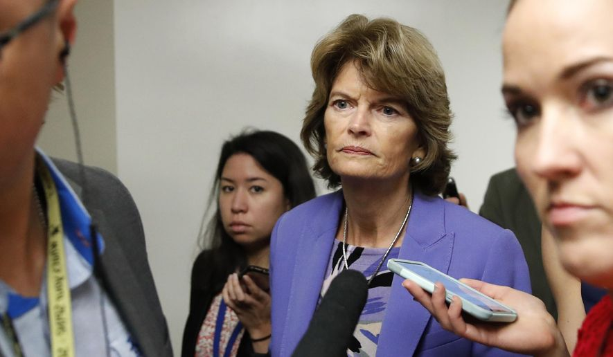 Sen. Lisa Murkowski, R-Alaska, walks on Capitol Hill, Wednesday, Oct. 3, 2018 in Washington, as reporters ask her questions. (AP Photo/Alex Brandon)