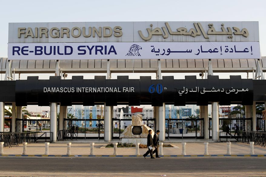 In this Tuesday, Oct. 2, 2018, photo, Chinese visitors arrive to the opening of the Syria rebuilding exhibition at the fair grounds in Damascus, Syria. With back-to-back trade fairs held in Damascus this month, Syria hopes to jumpstart reconstruction of its devastated cities by inviting international investors to take part in lucrative opportunities. (AP Photo/Hassan Ammar)