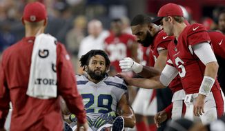 FILE - In this Sept. 30, 2018, file photo, Seattle Seahawks defensive back Earl Thomas (29) is greeted by Arizona Cardinals players as he leaves the field after breaking his leg during the second half of an NFL football game in Glendale, Ariz. The Seahawks won 20-17. The Seahawks face the Los Angeles Rams and running back Todd Gurley this week. (AP Photo/Ross D. Franklin, File) **FILE**