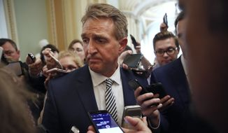 Sen. Jeff Flake, R- Ariz., pauses while he is questioned by reporters about Supreme Court nominee Brett Kavanaugh, Friday Sept. 28, 2018, on Capitol Hill in Washington. (AP Photo/Jacquelyn Martin) ** FILE **