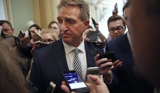 Sen. Jeff Flake, R- Ariz., pauses while he is questioned by reporters about Supreme Court nominee Brett Kavanaugh, Friday Sept. 28, 2018, on Capitol Hill in Washington. After a flurry of last-minute negotiations, the Senate Judiciary Committee advanced Brett Kavanaugh's nomination for the Supreme Court after agreeing to a late call from Sen. Flake for a one week investigation into sexual assault allegation against the high court nominee. (AP Photo/Jacquelyn Martin)
