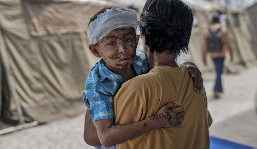 A boy injured during the tsunami is carried by his relative at a makeshift hospital in Palu, Central Sulawesi, Indonesia, Thursday, Oct. 4, 2018. People living in tents and shelters have little but uncertainty since the powerful earthquake and tsunami hit the city, where death toll rises and efforts to retrieve scores more victims buried deep in mud and rubble were still hampered Thursday by the lack of heavy equipment. (AP Photo/Fauzy Chaniago)
