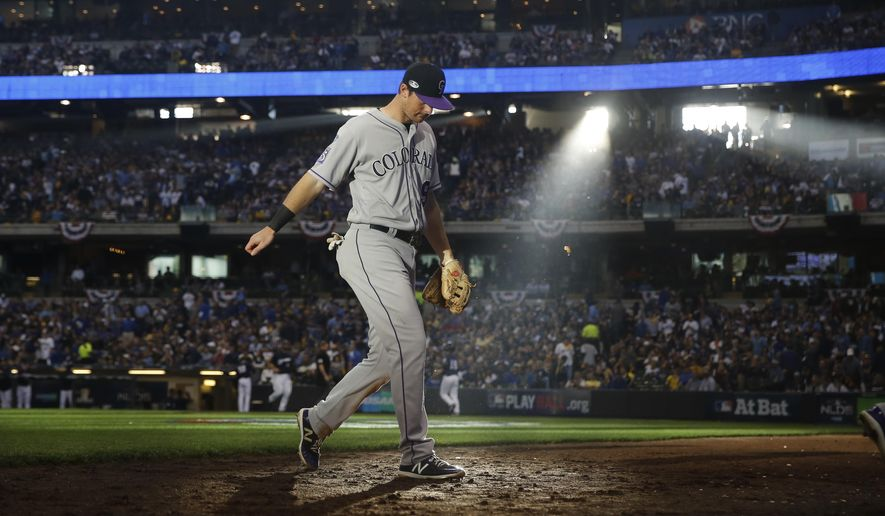 Colorado Rockies second baseman DJ LeMahieu walks off the field at the end of the fourth inning of Game 1 of the National League Divisional Series baseball game against the Milwaukee Brewers Thursday, Oct. 4, 2018, in Milwaukee. (AP Photo/Jeff Roberson)
