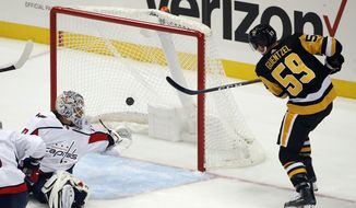 Pittsburgh Penguins' Jake Guentzel (59) gets the put behind Washington Capitals goaltender Braden Holtby for a goal during the first period of an NHL hockey game in Pittsburgh, Thursday, Oct. 4, 2018. (AP Photo/Gene J. Puskar)