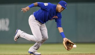 FILE - In this Sept. 8, 2018, file photo, Chicago Cubs shortstop Addison Russell fields a ground ball by Washington Nationals' Anthony Rendon during the fifth inning of the first baseball game of a doubleheader, Saturday, Sept. 8, 2018, in Washington. Rendon was out at first. Russell has accepted a 40-game suspension for violating Major League Baseball's domestic violence policy. Commissioner Rob Manfred announced the ban in a statement Wednesday, Oct. 3, 2018. Russell's unpaid suspension includes the 11 regular-season games he missed after being placed on administrative leave Sept. 21. Russell will be eligible to return on May 3 against St. Louis, barring any postponements. (AP Photo/Nick Wass, File)