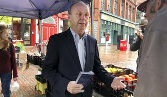In this Sept. 26, 2018 photo, independent candidate for governor, economic consultant Alan Caron talks to voters at a farmers market in Portland, Maine. Caron will face Democrat Janet Mills, Republican Shawn Moody and independent candidate Terry Hayes in the November general election. (AP Photo/Marina Villeneuve)