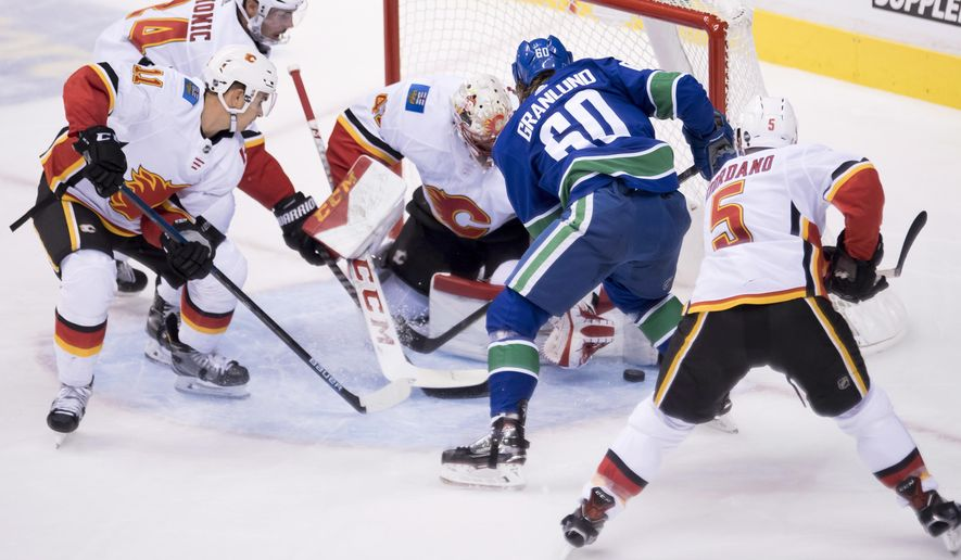 Vancouver Canucks center Markus Granlund (60) fails to get a shot past Calgary Flames goaltender Mike Smith (41) during the second period of an NHL hockey game Wednesday, Oct. 3, 2018, in Vancouver, British Columbia. (Jonathan Hayward/The Canadian Press via AP)