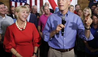 FILE - In this Monday, April 9, 2018, file photo, Florida Gov. Rick Scott, with his wife, Ann, announces his bid to run for the U.S. Senate at a news conference, in Orlando, Fla. Multimillionaire Scott maintains that he does not have any say over his fortune, but questions are mounting over his finances. (AP Photo/John Raoux, File)