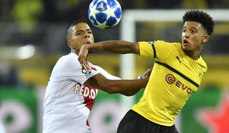 Dortmund's Jadon Sancho, right, fights for the ball with Monaco defender Benjamin Henrichs during the Champions League group A soccer match between Borussia Dortmund and AS Monaco in Dortmund, Germany, Wednesday, Oct. 3, 2018. (AP Photo/Martin Meissner)