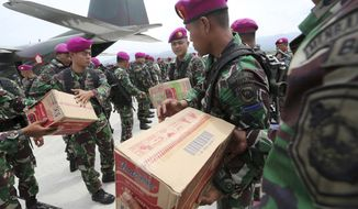 Indonesian military personnel distribute relief aid at the Mutiara Sis Al-Jufri airport to evacuate the earthquake and tsunami-damaged city of Palu, Central Sulawesi Indonesia, Thursday, Oct. 4, 2018. Life is on hold for thousands living in tents and shelters in the Indonesian city hit by a powerful earthquake and tsunami, unsure when they'll be able to rebuild and spending hours each day often futilely trying to secure necessities such as fuel for generators. (AP Photo/Tatan Syuflana)