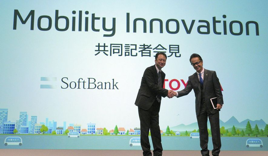 Representative Director and CTO of SoftBank Corp. Junichi Miyakawa, left and Executive Vice President of Toyota Motor Corporation Shigeki Tomoyama, right, shake hands during a press conference in Tokyo Thursday, Oct. 4, 2018. Japan's No. 1 automaker Toyota Motor Corp. and Japanese technology giant SoftBank Group Corp. say they are setting up a joint venture to create mobility services. (AP Photo/Eugene Hoshiko)