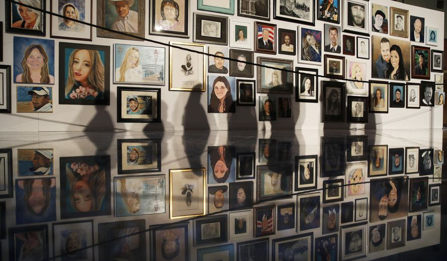 In this Sept. 17, 2018 file photo, people's shadows fall upon portraits of victims of the mass shooting of the Oct. 1, 2017, mass shooting in Las Vegas on display at the Clark County Government Center in Las Vegas. (AP Photo/John Locher, File)