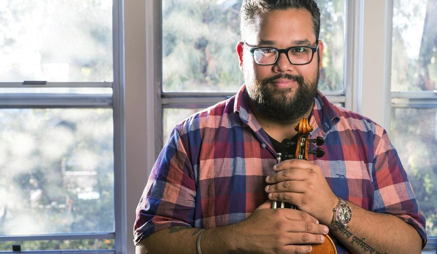 This Sept. 18, 2018 photo Provided by the John D. and Catherine T. MacArthur Foundation shows Robert Vijay Gupta, the Mark Houston Dalzell and James Dao-Dalzell First Chair Violin with the Los Angeles Philharmonic and Founder and Artistic Director of Street Symphony posing with his violin in his house in Los Angeles. The John D. and Catherine T. MacArthur Foundation on Thursday Oct. 4, 2018 named Gupta and 24 other academics, activists, artists, scholars and scientists, MacArthur fellows. The recipients will receive $625,000 over five years to use as they please. (Photo by John D. and Catherine T. MacArthur Foundation via AP)