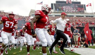 FILE - In this Sept. 8, 2018, file photo, Nebraska head coach Scott Frost leads his players onto the field before an NCAA college football game against Colorado in Lincoln, Neb., Saturday, Sept. 8, 2018. Nebraska's worst start since 1945 has been a major national storyline this season, especially after the splash hire of 2017 national coach of the year Scott Frost. The Huskers have lost 14 of their last 18 games, and last weekend they dropped an eighth in a row for the first time in the program's 129-year history. (AP Photo/Nati Harnik)