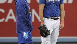 Los Angeles Dodgers manager Dave Roberts, left, talks to starting pitcher Clayton Kershaw during baseball practice Wednesday, Oct. 3, 2018, in Los Angeles for Thursday's Game 1 of the National League Division Series against the Atlanta Braves. (AP Photo/Jae C. Hong)